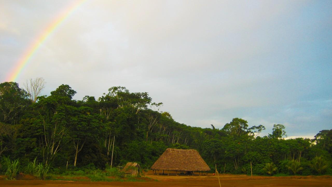 achuar village with rainbow