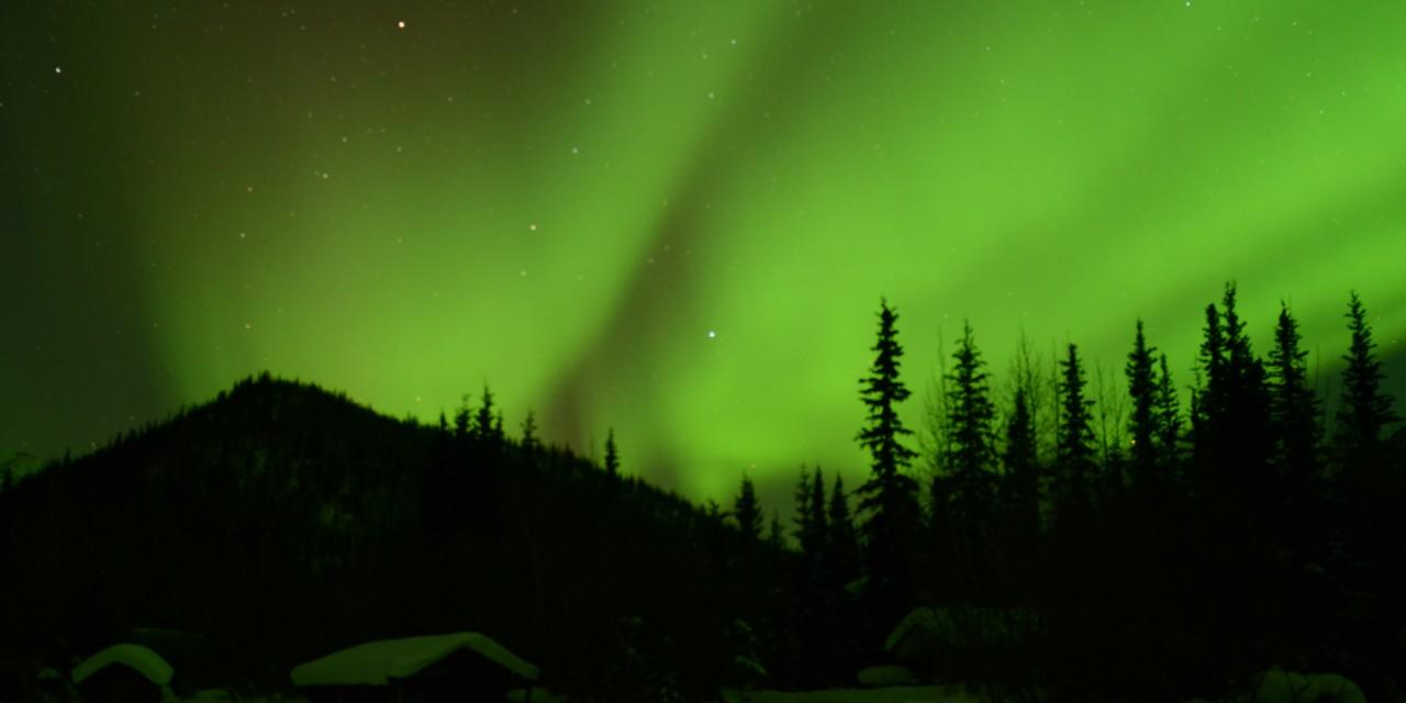 Lights dance above a cabin